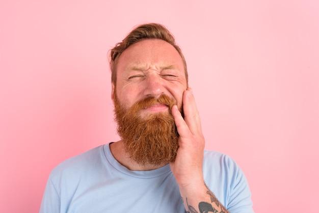 Homem feliz com camiseta azul claro está com dor nos dentes