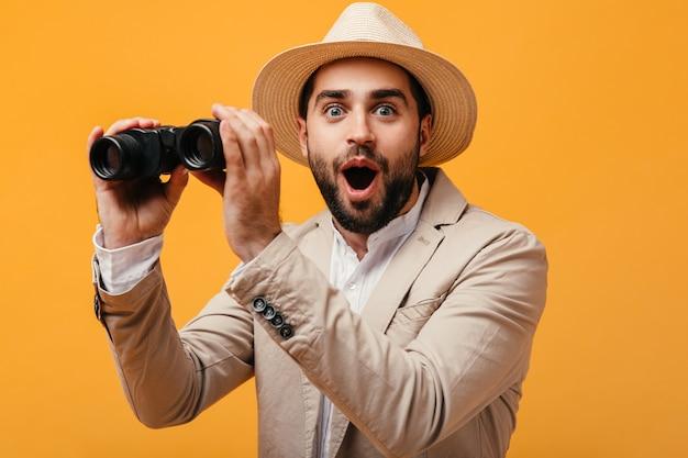 Homem feliz com chapéu e terno bege segurando um binóculo