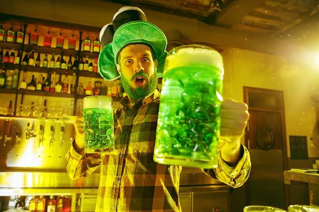 Homem feliz com copo de cerveja olhando para o lado no bar