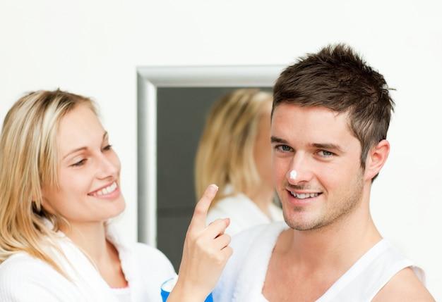 Homem feliz com creme no nariz com a namorada
