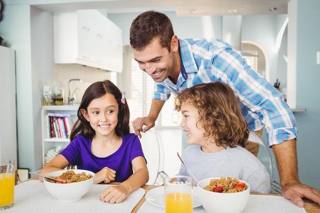 Homem feliz com crianças tomando café da manhã