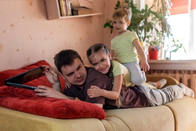 Homem feliz com crianças usando laptop e fone de ouvido durante o trabalho em casa, a vida em quarentena