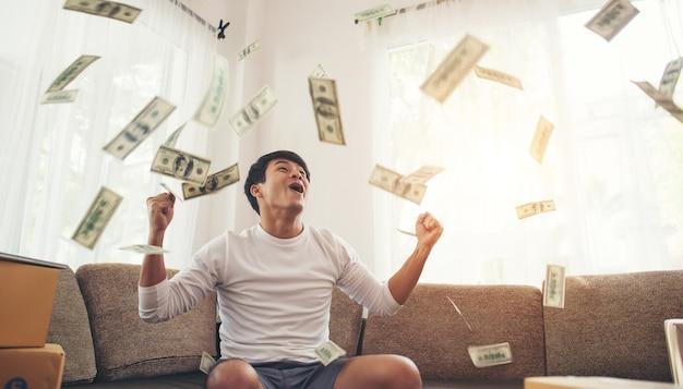 Homem feliz com dinheiro dólares voando no escritório em casa, rico do conceito on-line de negócios