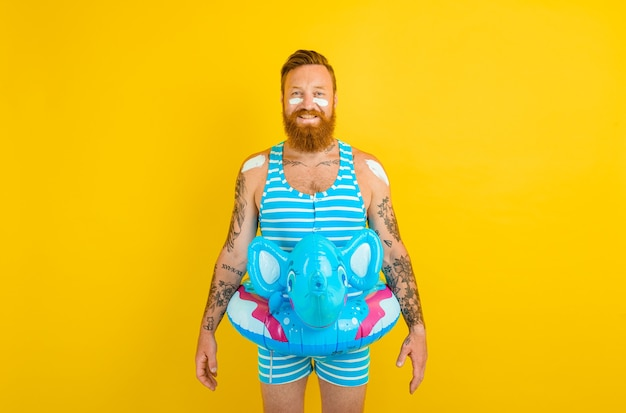 Homem feliz com donut inflável com elefante pronto para nadar