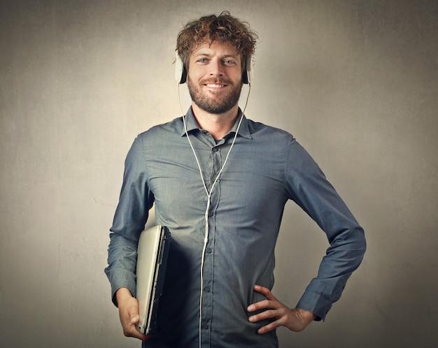 Homem feliz com fones de ouvido e laptop