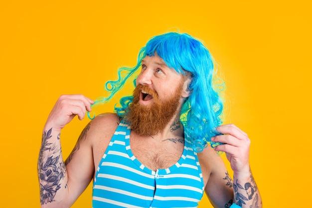 Homem feliz com maiô com bóia salva-vidas e peruca azul age como uma mulher feliz