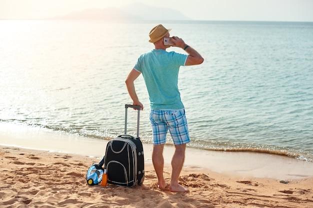 Homem feliz com mala e celular em pé na praia freelancer. Foto Premium