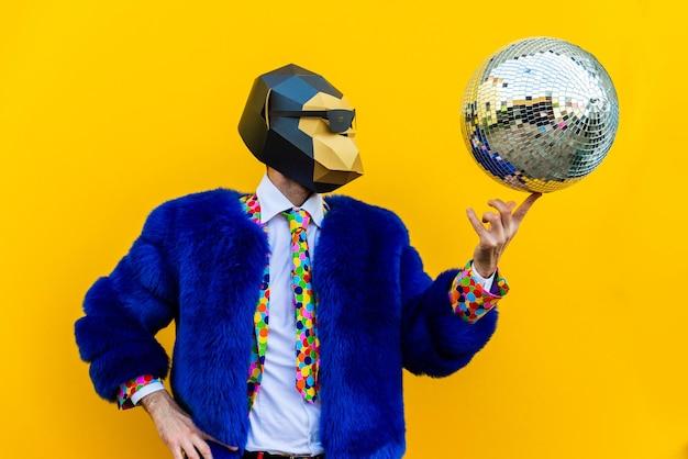 Homem feliz com máscara engraçada de poliéster na parede colorida