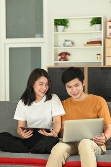 Homem feliz com namorada sorridente relaxando no sofá em casa