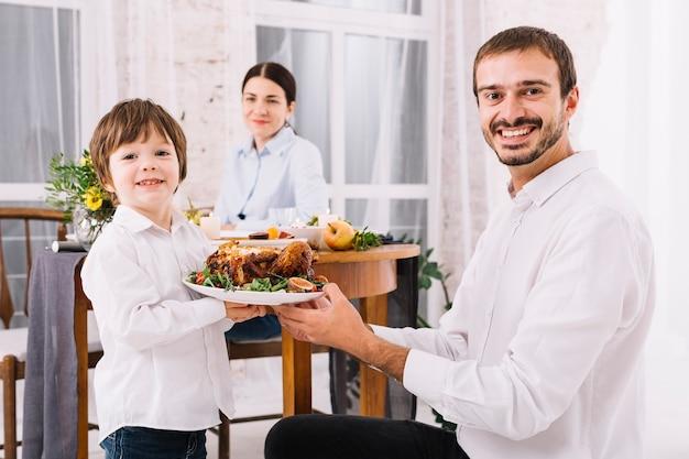 Homem feliz com o filho segurando o frango no prato