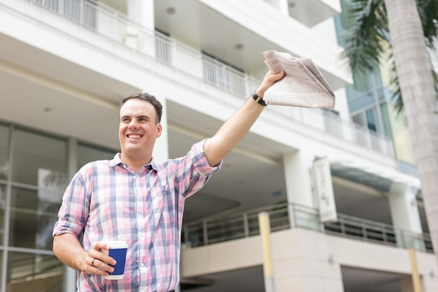 Homem feliz com o jornal hailing taxy on street