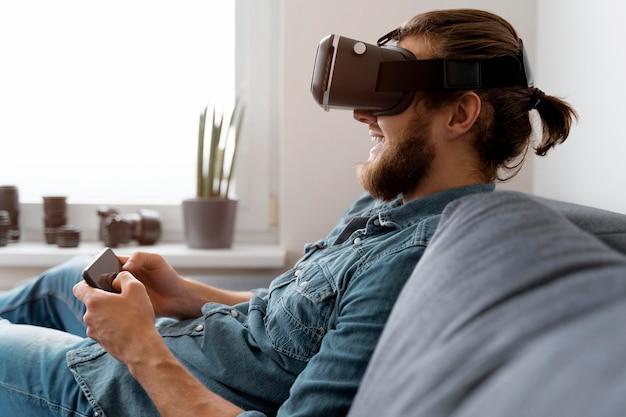 Homem feliz com óculos vr segurando um telefone