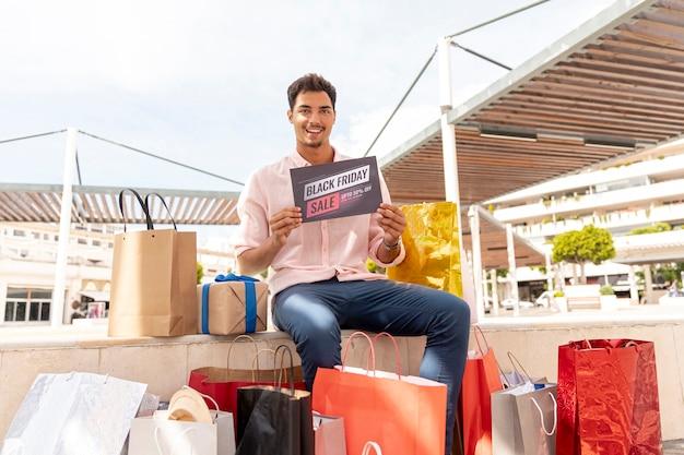Homem feliz com sacolas de compras