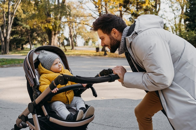 Homem feliz com seu filho lá fora no carrinho