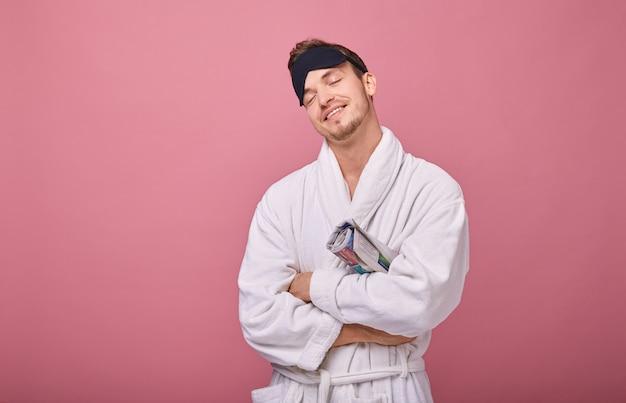 Homem feliz com sono na máscara de dormir na cabeça em roupão com cinto amarrado com jornal debaixo do braço