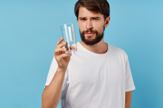 Homem feliz com um copo de água no estilo de vida de bebida de parede azul.