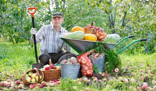 Homem feliz com uma colheita no jardim