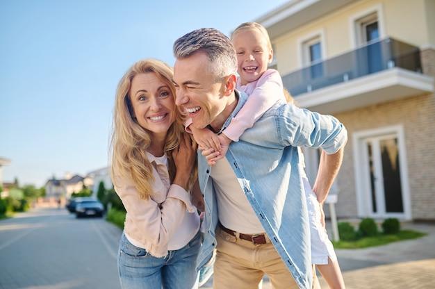 Homem feliz com uma garota e uma mulher andando na rua