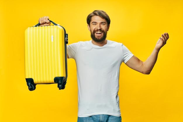 Homem feliz com uma mala amarela viaja pelo mundo