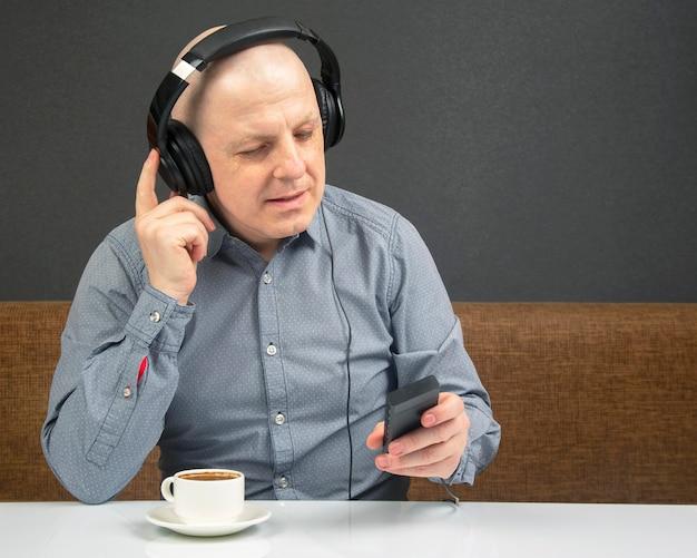 Homem feliz com uma xícara de café em fones de ouvido portáteis ouve música usando um player.