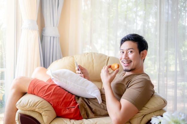Homem feliz comer biscoitos no sofá.