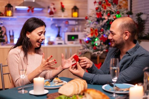 Homem feliz conquistando namorada com anel de noivado caro de luxo com diamante