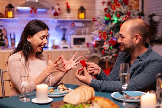 Homem feliz conquistando namorada com anel de noivado de diamante de luxo