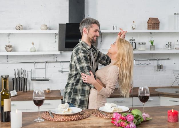 Homem feliz dançando com mulher loira perto de mesa na cozinha