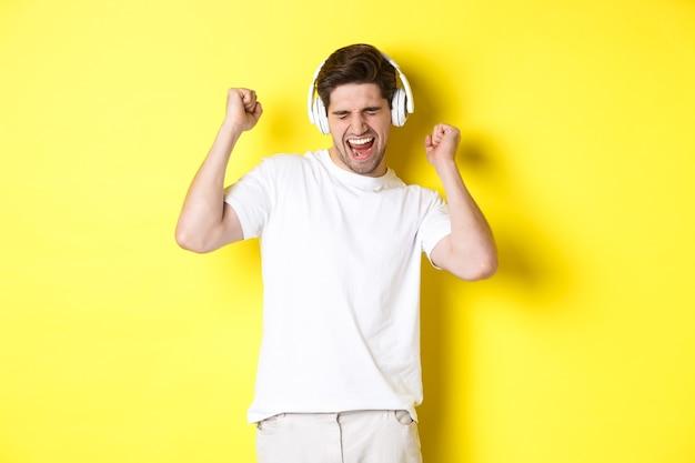 Homem feliz dançando e ouvindo música em fones de ouvido brancos, em pé sobre a parede amarela