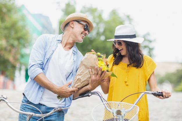 Homem feliz dando buquê para mulher