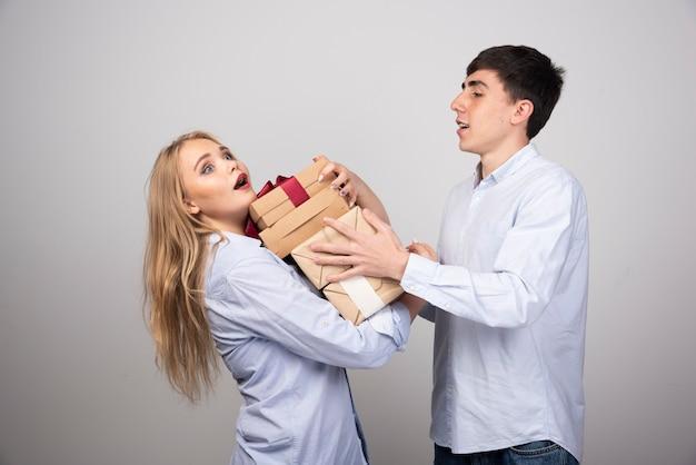 Homem feliz dando caixas de presente para a namorada contra uma parede cinza.
