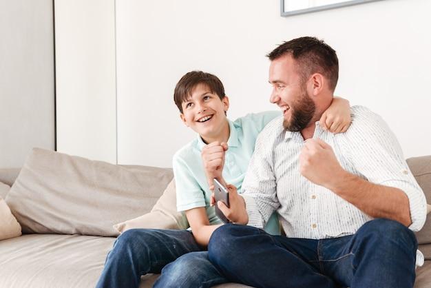 Homem feliz de 30 anos e menino de 8 a 10 sentados juntos no sofá em casa e se alegrando com os punhos cerrados
