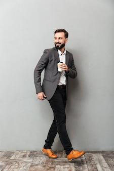 Homem feliz de corpo inteiro com café para viagem sorrindo e andando cinza