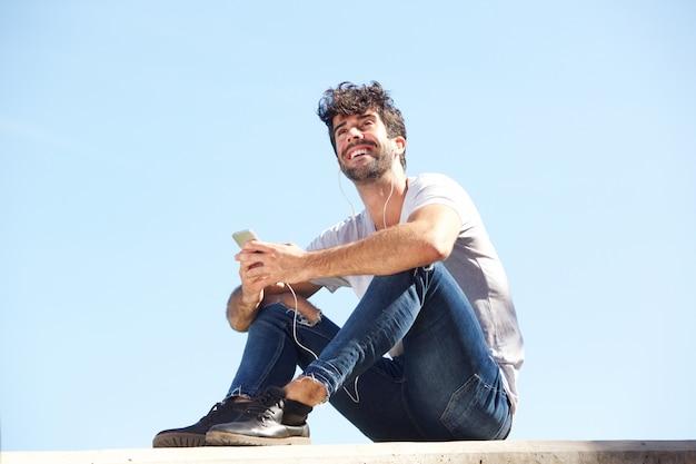 Homem feliz de corpo inteiro sentado na parede com fones de ouvido e celular