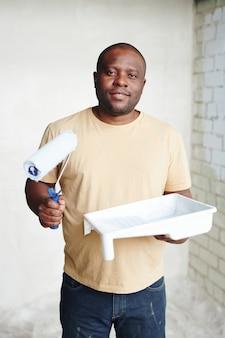 Homem feliz de etnia africana com o pintor e o recipiente de plástico quadrado branco com tinta encostada no canto de duas paredes