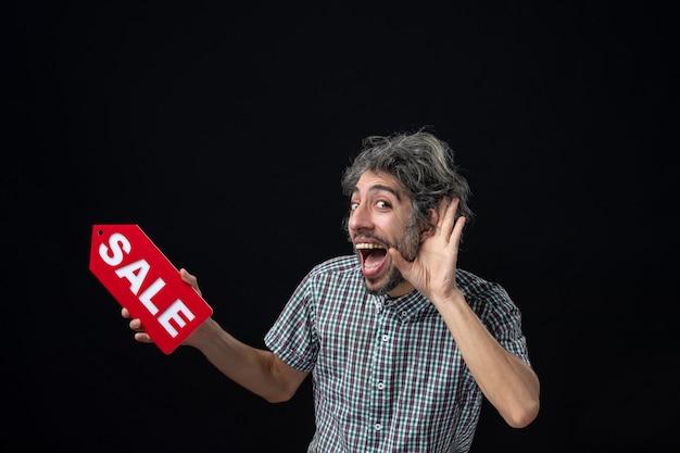 Homem feliz de frente ouvindo algo segurando uma placa vermelha de venda na parede escura