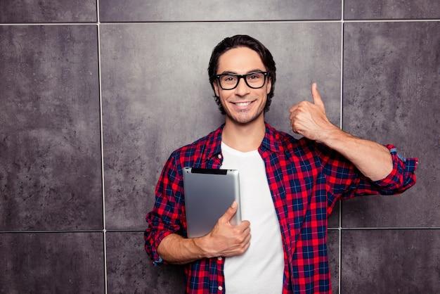 Homem feliz de óculos segurando um tablet e mostrando o polegar