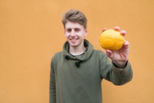 Homem feliz, de pé em uma parede laranja com limão nas mãos. concentre-se em limão