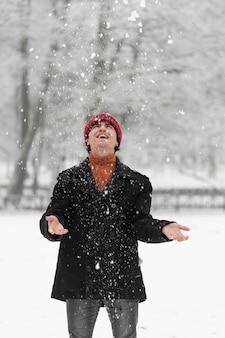 Homem feliz, de pé na neve