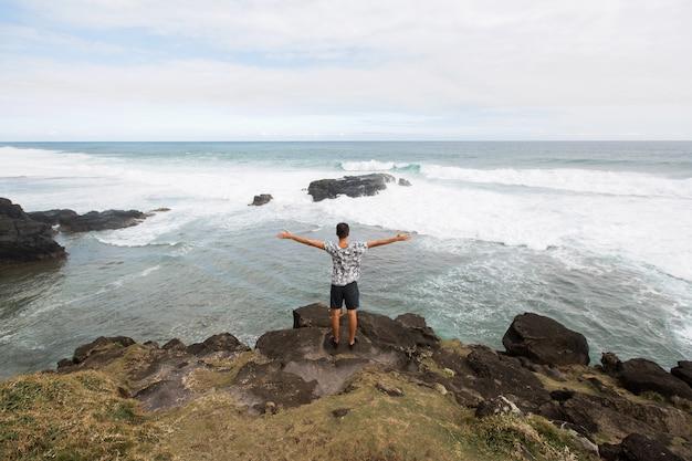 Homem feliz, de pé no pico da montanha, com vista para o oceano. sucesso, vencedor, felicidade.