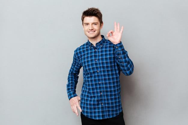 Homem feliz, de pé sobre uma parede cinza e mostrando o gesto certo