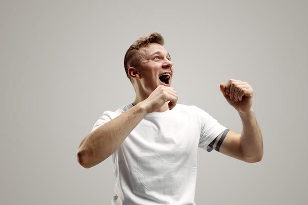 Homem feliz de sucesso vencedor comemorando ser um vencedor. imagem dinâmica do modelo masculino caucasiano em fundo cinza do estúdio. vitória, conceito de prazer. conceito de emoções faciais humanas.