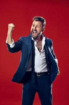 Homem feliz de sucesso vencedor comemorando ser um vencedor. imagem dinâmica do modelo masculino caucasiano em fundo vermelho do estúdio.