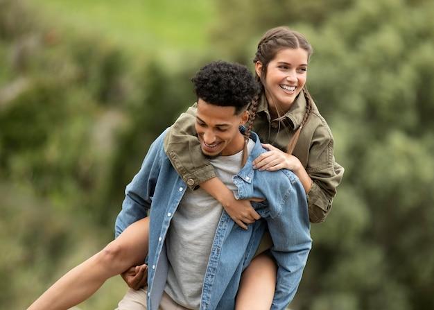 Homem feliz de tiro médio carregando mulher