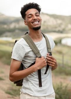 Homem feliz de tiro médio usando mochila