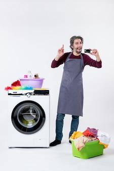Homem feliz de vista frontal segurando um cartão em pé perto da máquina de lavar no fundo branco