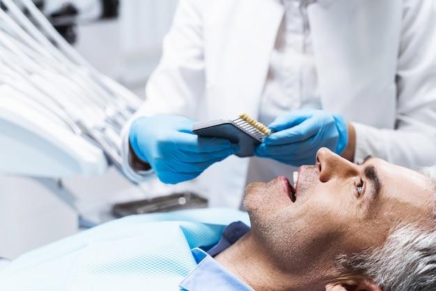 Homem feliz deitado na cadeira do dentista enquanto o médico trata os dentes antes do clareamento