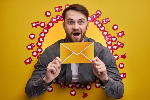 Homem feliz, desfrutando de feedback positivo, quer mais assinantes e mensagens, segurando a carta nas mãos.