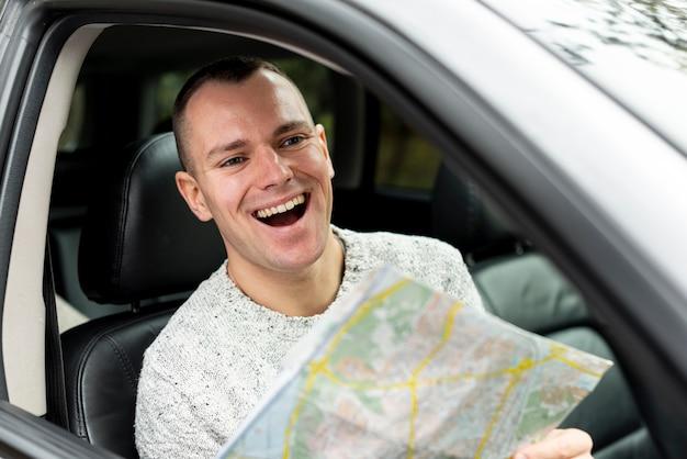 Homem feliz dirigindo e segurando um mapa