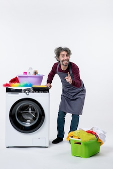 Homem feliz dona de casa em vista frontal em pé perto do cesto de roupa suja da máquina de lavar branca no chão